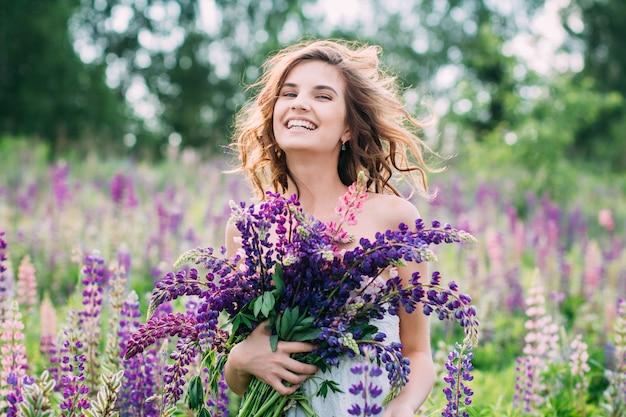 フィールド上のルピナスの花束を持つ少女