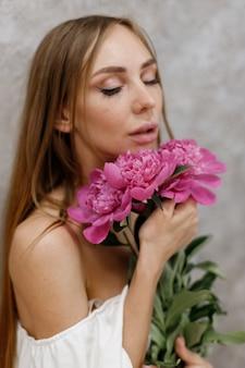 灰色の背景のクローズアップで牡丹の花束を持つ少女