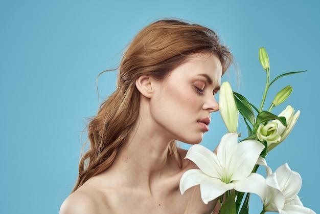 青い背景の赤い髪の肖像画モデルに白い花の花束を持つ少女