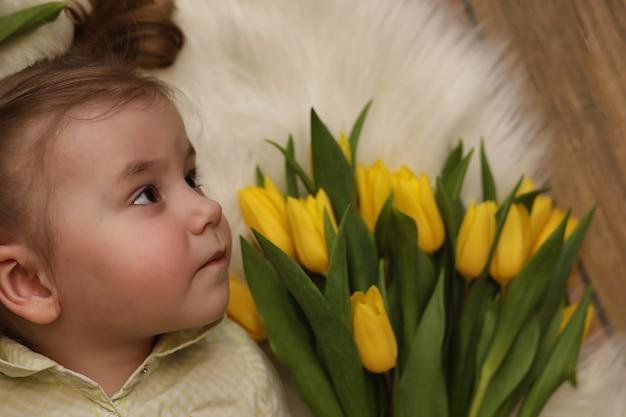 Девушка с букетом желтых тюльпанов. девушка с подарком цветы в вазе. подарок девушкам на женский праздник с желтыми тюльпанами на полу.