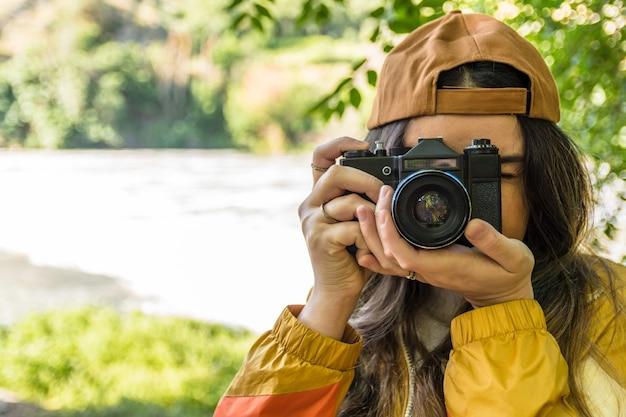 모자와 자연 속에서 그녀의 빈티지 카메라로 사진을 찍는 황금 스포츠 재킷 소녀. 강변. 라이프 스타일 컨셉