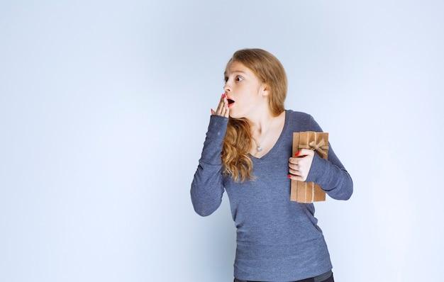 Девушка с картонной подарочной коробкой выглядит напуганной и взволнованной.