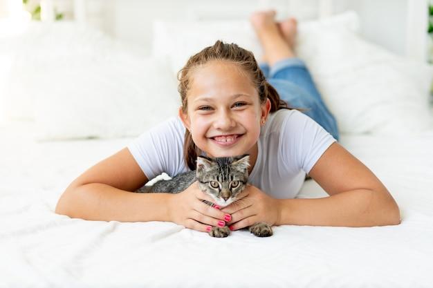 猫と女の子がベッドに横たわっています