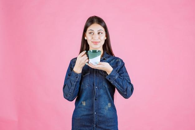 커피 컵 미소와 긍정적 인 느낌을 가진 소녀
