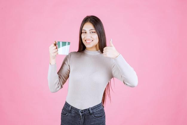 즐거움 기호를 만드는 커피 잔을 가진 소녀