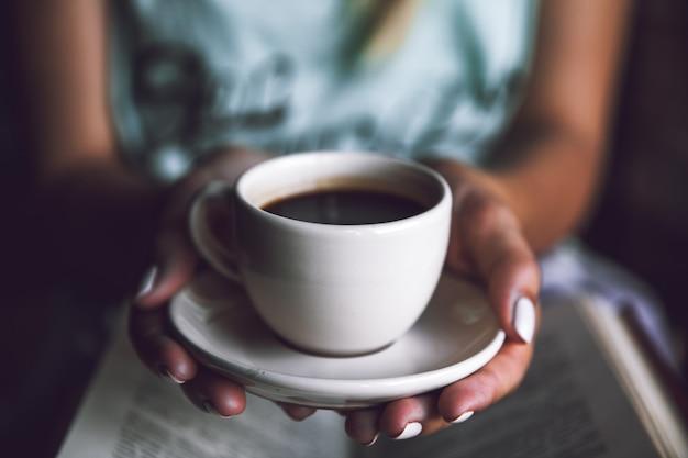 一杯のコーヒーと本を持つ少女。目覚め、朝、休憩、趣味