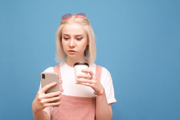Девушка с чашкой кофе в руках, использовать смартфон на синем.