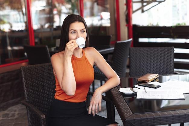 カフェに座っているコーヒーのカップを持つ少女。広い笑顔。きれいな肌に。ドキュメントに署名した後のビジネスの女性。ビジネスミーティング。