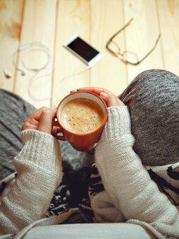 Девушка с чашкой кофе, сидя на деревянном полу