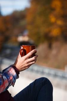 バルコニーの手すりに座っているコーヒーのカップを持つ少女。山小屋の朝