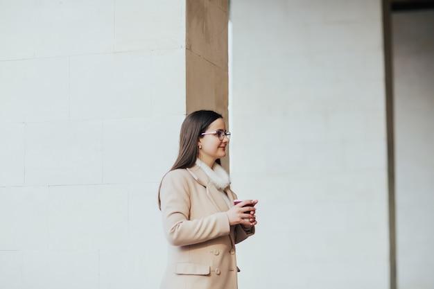 Девушка с чашкой кофе гуляет по городу