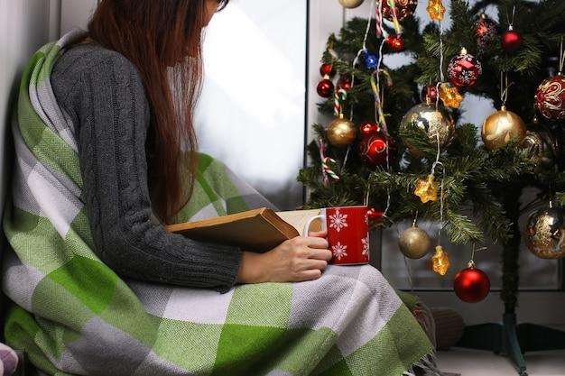 大晦日の窓際に温かい飲み物を片手に立っている女の子