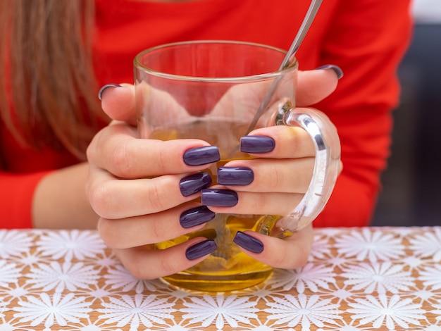 차 한잔과 함께 소녀입니다. 차 한 잔을 들고 아름다운 손톱을 가진 소녀
