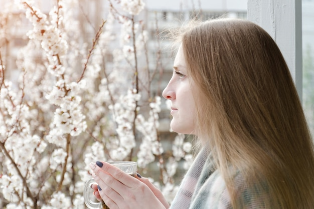 お茶を片手に窓際に立って遠くを見つめる少女。背景に咲く木