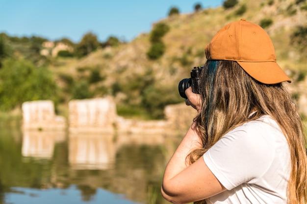 자연 속에서 그녀의 빈티지 카메라로 사진을 찍는 찬장 소녀. 강변. 라이프 스타일 컨셉