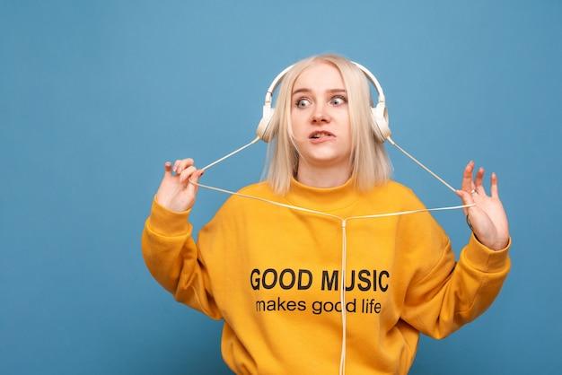 실망한 재미있는 얼굴을 가진 소녀가 헤드폰으로 음악을 듣는다.