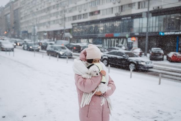 街の通りの雪の上で犬を腕に抱えた少女が降っています