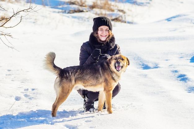 冬の散歩に犬を持つ少女。少女と白い雪を背景に犬