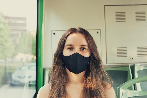 도시 버스를 타고 여행하는 얼굴 마스크와 소녀