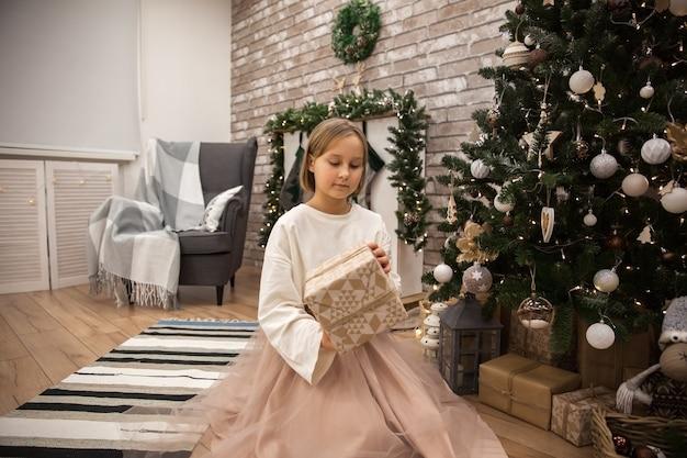 クリスマスツリー、ソフトフォーカスで贈り物を持つ女の子