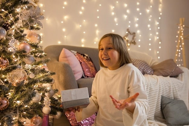 クリスマスツリーで贈り物を持つ女の子