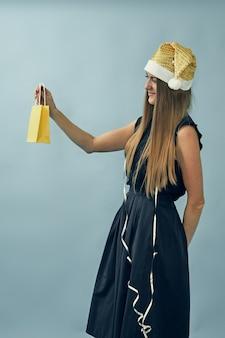 Девушка с подарочным пакетом в руках и в шляпе санта-клауса