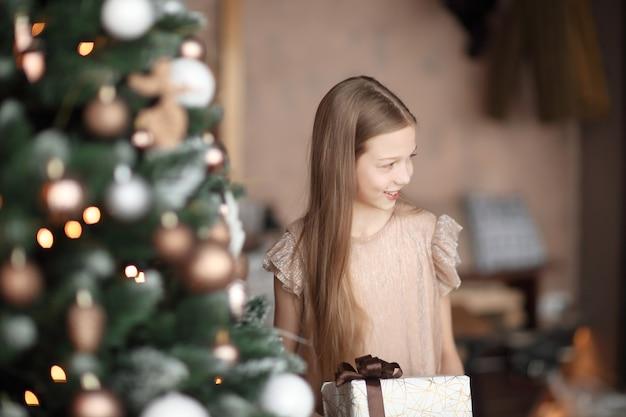 クリスマスツリーの近くに立っているギフトボックスを持つ女の子