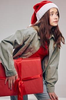 Девушка с подарочной коробкой перевязана красной лентой праздники рождество новый гольф санта шляпа. фото высокого качества