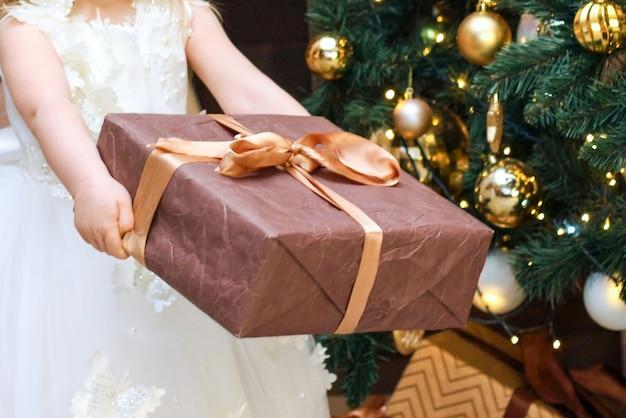 Девушка с подарком в руках возле елки