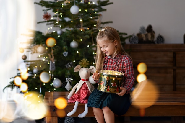 贈り物を持った女の子がクリスマスツリーの近くに座っています
