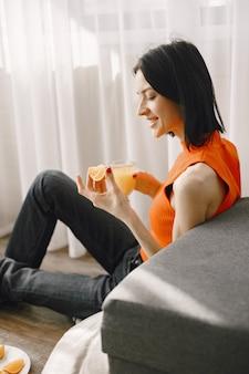 바닥에 앉아 주스 한 잔 소녀.