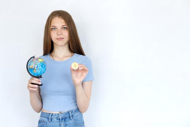 灰色の背景に地球儀とビットコインを持つ少女。オンラインで作業する