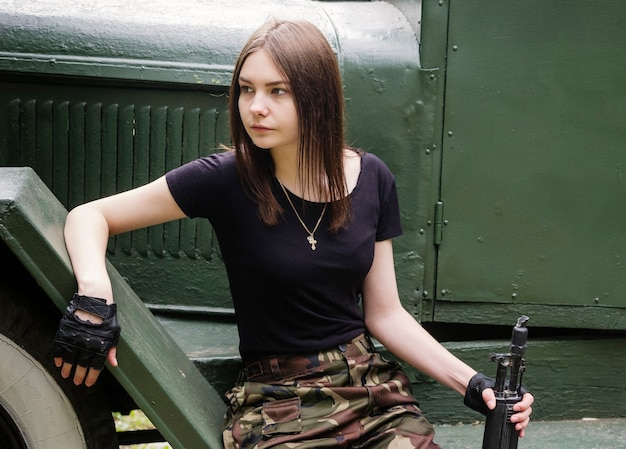 軍のトラックの階段に座っている銃を持つ少女