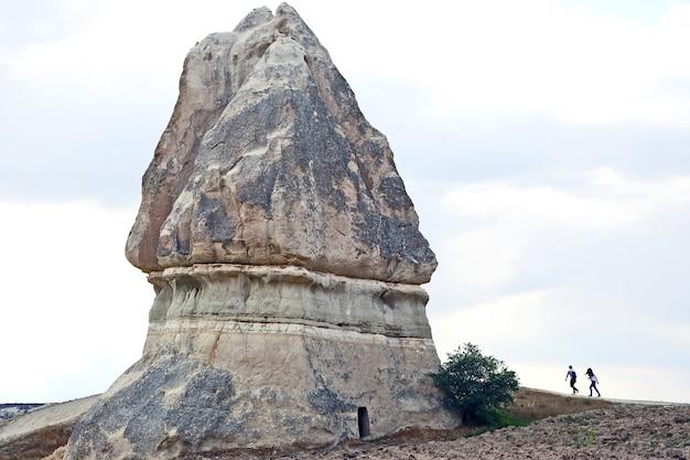 Девушка с парнем идут к большой скале