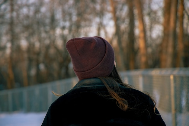 Девушка в шляпе стоит в лесу днем