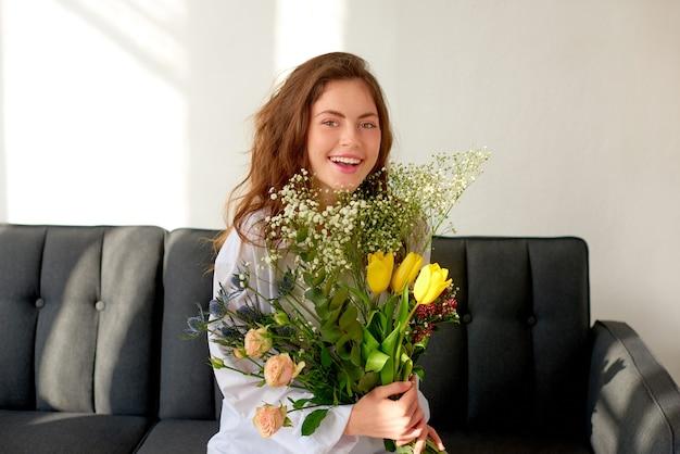 Девушка с огромным букетом весенних полевых цветов в руках радуется и смеется, сидя на диване у себя дома