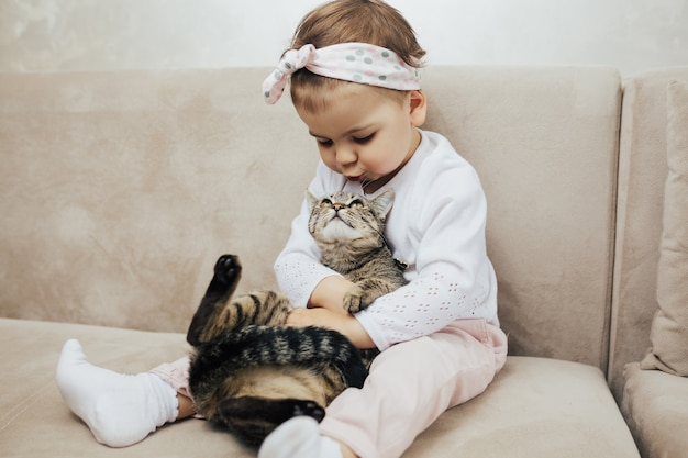 リビングルームのソファに座っている手に子猫を持つ女の子 Premium写真