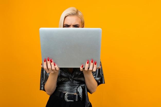 黄色のスタジオの背景に彼女の手でノートパソコンを持つ少女