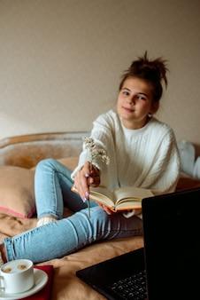 Девушка с ноутбуком в руках сидит на кровати.