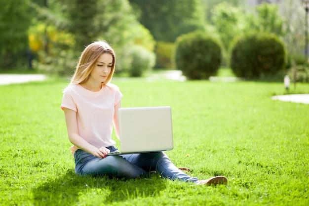 芝生の上に座っているラップトップを持つ少女