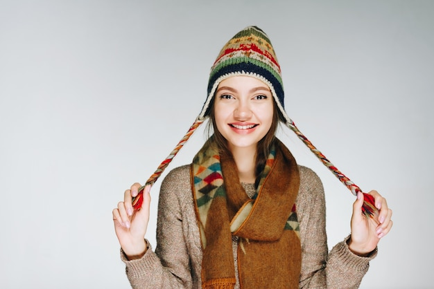 ふざけてポーズをとって帽子をかぶった素敵な笑顔の女の子