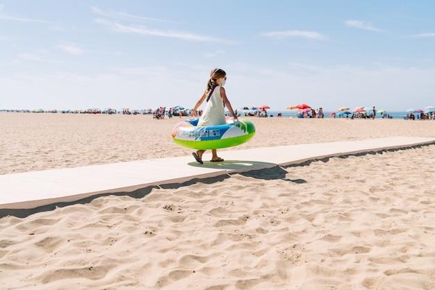그녀의 얼굴에 마스크를 쓰고 안경을 쓰고 팔에 다채로운 풍선 매트리스 바퀴를 달고 해변으로가는 길을 걷고있는 소녀는 코로나 19 코로나 바이러스 전염병 속에서 휴가를 즐기기 위해