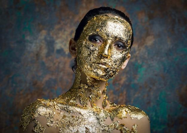 金箔で作られた彼女の顔にマスクを持つ少女抽象上のブルネットの暗いスタジオの肖像画