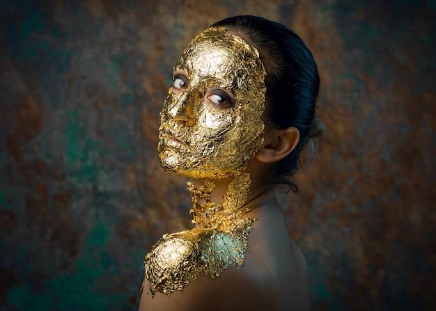 金箔で作られた彼女の顔にマスクを持つ少女。