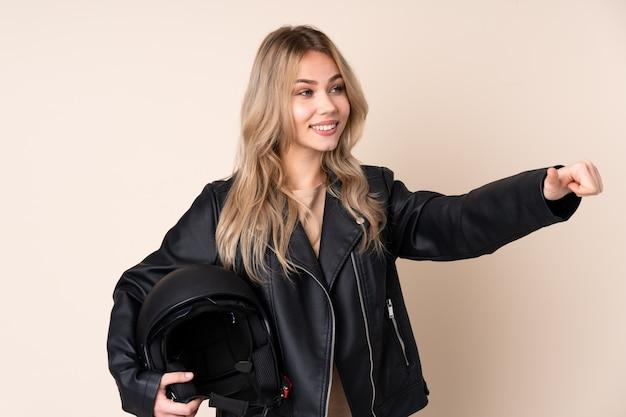 親指ジェスチャーを与えるベージュの壁にオートバイのヘルメットを持つ少女