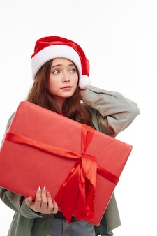 Девушка с новогодним подарком рождественская шляпа светлом фоне. фото высокого качества