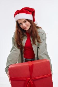 Девушка с новогодним подарком в шляпе санта улыбка праздник весело светлом фоне. фото высокого качества