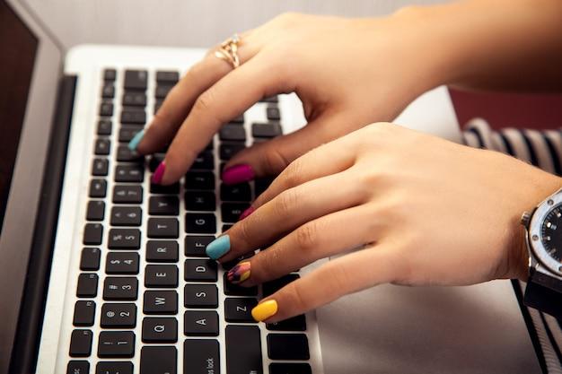 ノートパソコンの労働者で働いている素敵なマニキュアを持つ少女