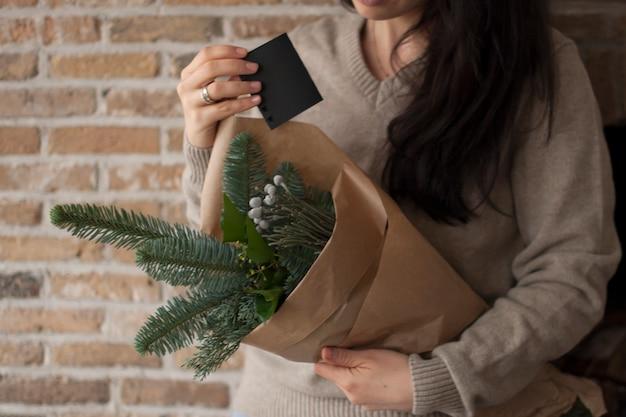 벽돌 벽 근처에 크리스마스 트리 분기의 무리와 함께 그녀의 손에 메모와 함께 소녀