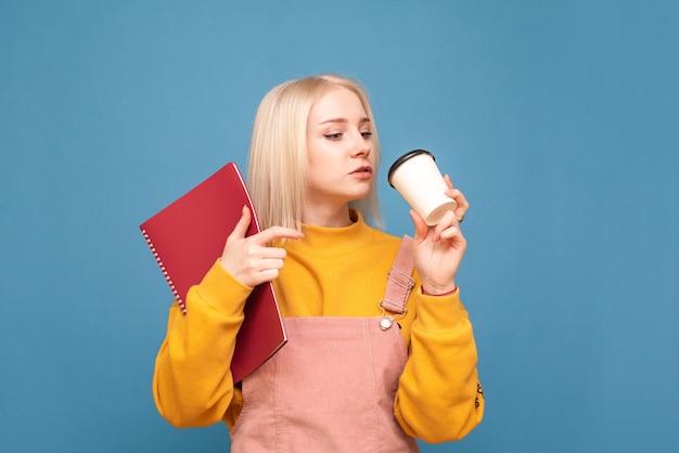 Девушка с ноутбуком и чашкой кофе, изолированные на синем